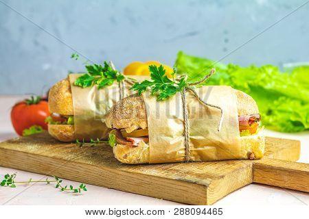 Italian Porchetta Sandwich. Ciabatta Sandwich With Ham, Tomato, Cheese, Pepper, Onion And Salad On W