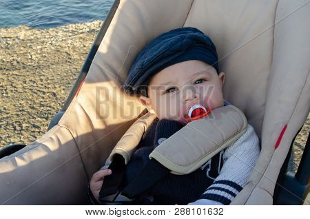 Cute 4 Months Old Baby Boy Sitting In The Pushchair On The Beach With Blue Hat And Red Pacifier.