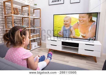 Close-up Of Innocent Girl Sitting On Sofa Watching Television In Living Room