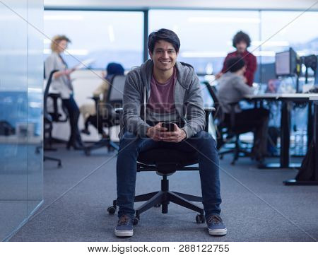young indian male software developer using mobile phone writing messages while having break at modern creative startup office