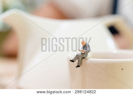 Miniature People : Businessman Reading A Book On A Cup Of Tea And Copy Space For Text
