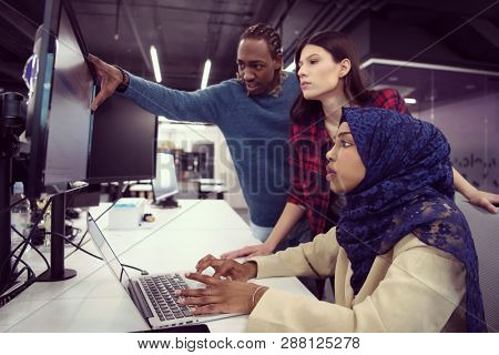 young multiethnics business team of software developers working together using laptop computer while writing programming code at modern startup office