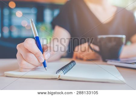 Business Woman Hand Is Writing On A Notebook With A Pen.