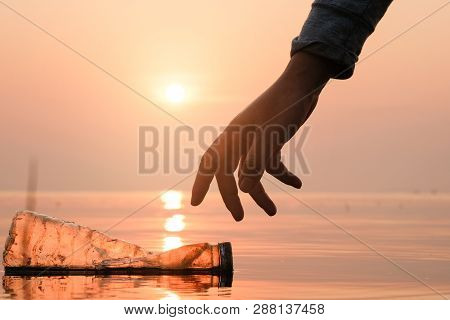 Hand Woman Picking Up Empty Of Plastic Bottle Cleaning On The Beach , Volunteer Concept. Environment