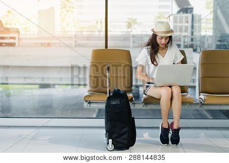 Asian Woman Teenager Using Laptop Computer At Airport Terminal Sitting With Luggage Suitcase And Bac