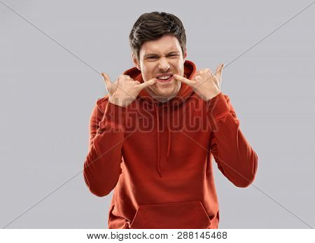 bullying, teasing and people concept - bully young man in red hoodie whistling over grey background