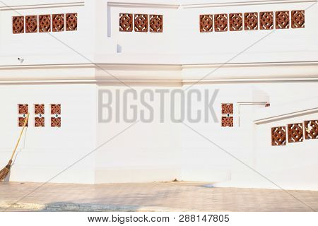 White Wall Of A Buddha Temple With Red Brick Blowholes On The Wall And Cement Ground Floor