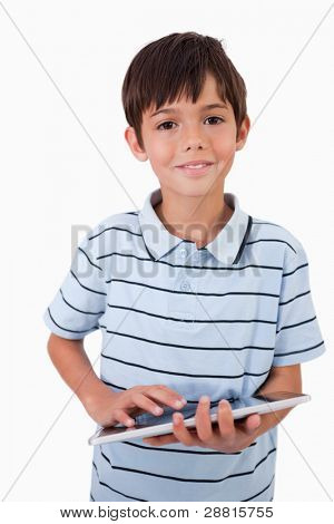 Portrait of a cheerful boy using a tablet computer against a white background
