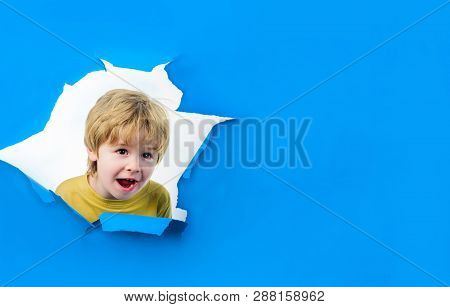 Smiling Boy Looking Through Hole In Paper Wall. Happy Child Boy Making Hole In Paper. Kid Looks Thro