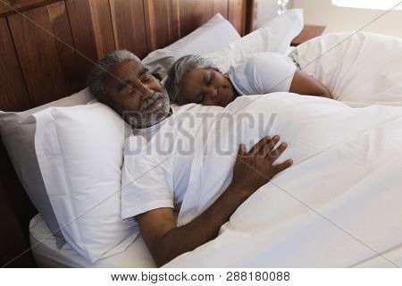 Close-up of a senior African American couple sleeping together in bedroom at home