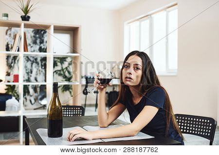 Alcoholism Is A Disease Of The Whole Person. Young Woman Drinking Red Wine Alone In Kitchen At Home.