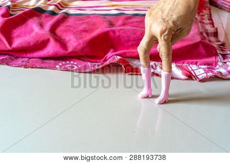 The Old Woman's Hand Plays Pink Plastic Boots Toy And Post It Like A Model's Post.