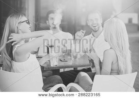 Man Vapor Hookah Pipe In Shisha Bar Lounge. Women Twins And Men Friends Relax In Cafe Outdoor. Celeb