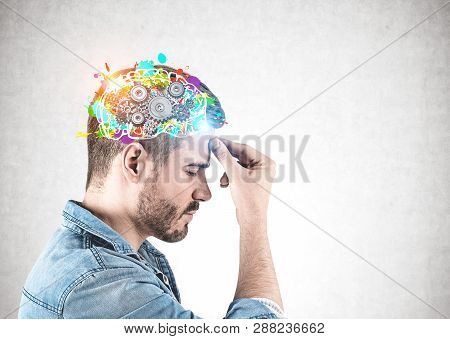 Side View Of Young Man With Beard Wearing Jeans Shirt And Thinking Hard With His Eyes Closed Standin