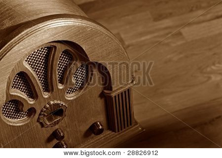 Vintage wooden radio on wood background with copy space.  Macro with shallow dof.