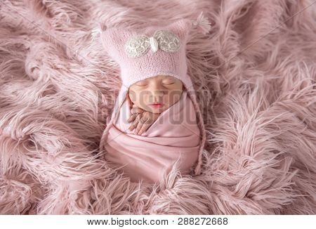 sleepy newborn in a cute beanie hat on a pink shaggy carpet