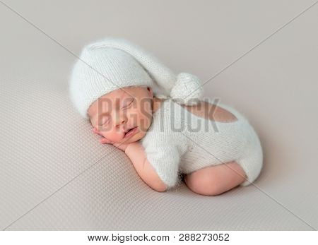 Cute little baby in white hat and knitted suit with toy sweetly sleeping