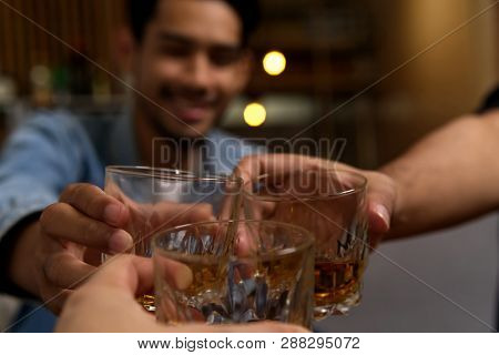 Close Up Shot Of Glasses Clinking Between Group Of Friends Drinking Whiskey At Night Party In Restau