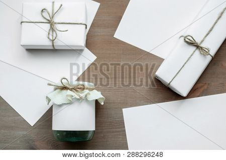 Green Glass Jar, White Paper And White Gift Boxes