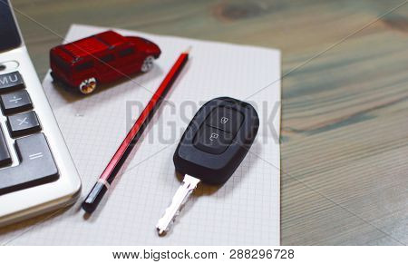 Calculator, Toy Car, Red Pencil, Car Keys And Notebook On Wooden Texture Background, Shallow Depth O