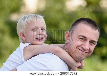 Happy Father With Little Son On Back Outdoors. Blurred Green Trees In The Distance. Concept Of Frien