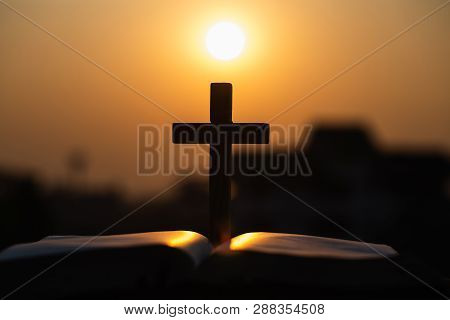Silhouette Of  Wooden Christian Cross On Bible With A Bright Sunrise As Background , God.