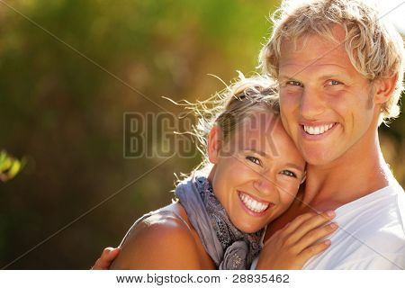 Happy young couple outdoors. Shallow DoF with focus on man.