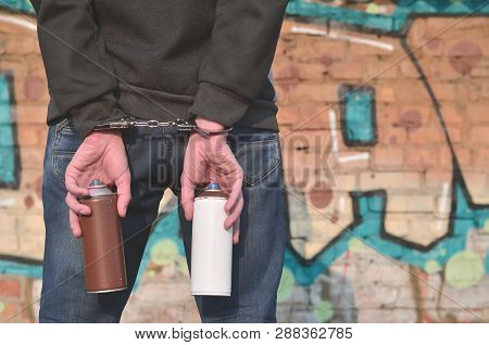 Young Hoodlum Caught By The Police And Shackled In Handcuffs Wit