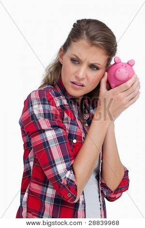 Portrait of a sad woman shaking a piggy bank against a white background