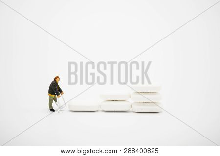 Miniature Of Old Man Broken Legs Model Around With Pharmaceutical Medicine Pills, Capsules And Table