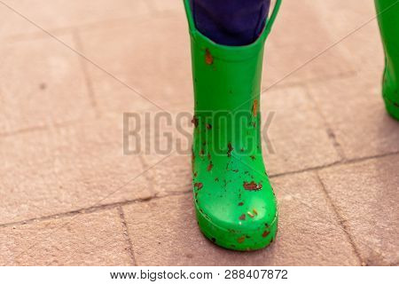 Small Childs Green Welly Covered In Dirt And Leaves