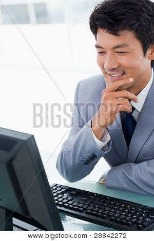Portrait of a smiling manager using a computer in his office