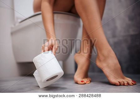 Young Woman Sit On Toilet And Get Rolled Paper From Floor. She Feel Sick. Well-built Legs Posing.