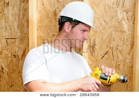 General Contractor Builder Using A Power Screw Driver While Building A New Home