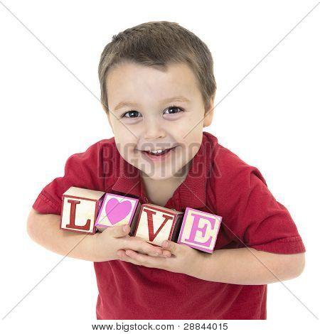 smiling little boy holding blocks that spell