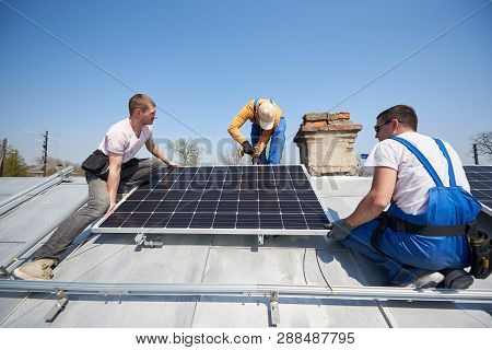 Male Workers Installing Stand-alone Solar Photovoltaic Panel System Using Screwdriver. Three Electri