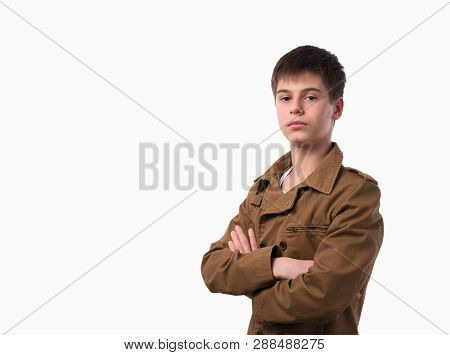 Portrait Of Caucasian Teen Boy On White Background With Folded Arms.