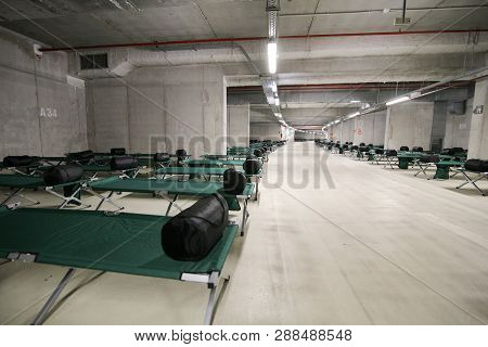 Camp folding cots and sleeping bags are being set up in the underground parking of a stadium and wait for refugees, during the drill of a catastrophic earthquake in the city in which there are many victims poster