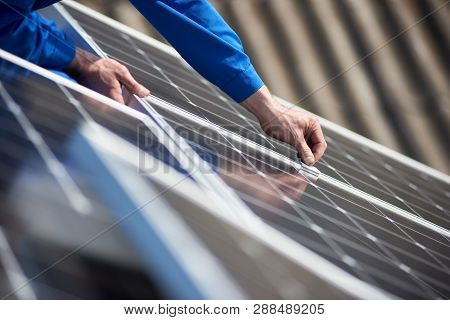 Male Engineer In Blue Suit Installing Solar Photovoltaic Panel System. Close Up View Of Electrician
