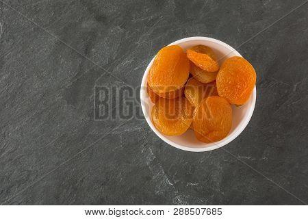 Tasty Dried Apricots On Darck Slite Background