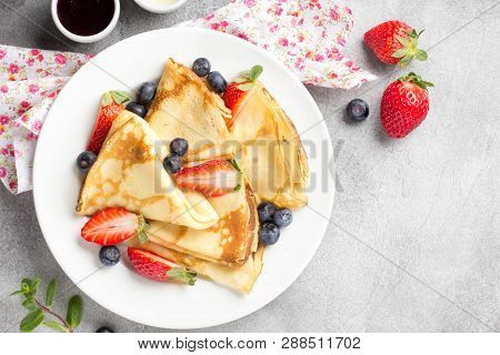 Thin Pancakes With Strawberries And Blueberries, Jam, Condensed Milk, Delicious Breakfast. Russian T