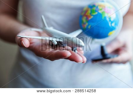 Female Woman Hands Holding Small Toy Model Plane And Globe Map. Travel By Plane Vacation Weekend Adv