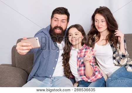 Use Smartphone For Selfie. Friendly Family Having Fun Together. Mom Dad And Daughter Relaxing On Cou