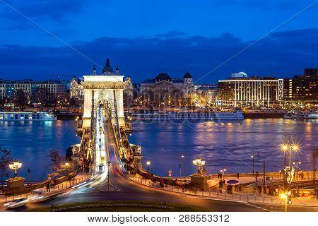 Nineteenth Century Chain Bridge (szechenyi Lanchid) And Budapest Cityscape At Night. Budapest, Hunga