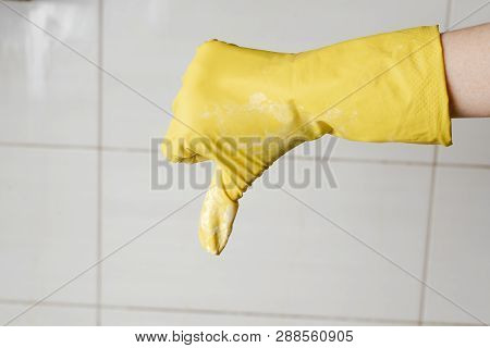 Hand In Yellow Rubber Glow Showing Thumb Down