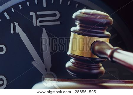 Wood And Brass Gavel Standing Upright On Its Base With A Clock Dial Showing Five To Twelve Behind In