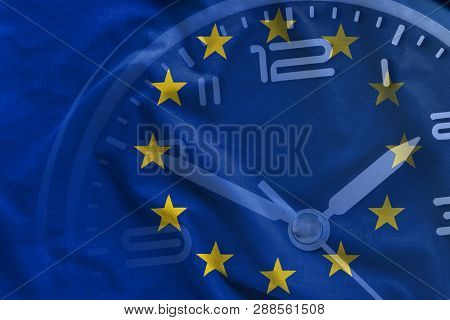 Overlay Of The Eu Flag And The Dial Of A Clock With Hands And Numerals Showing Five To Twelve In A C
