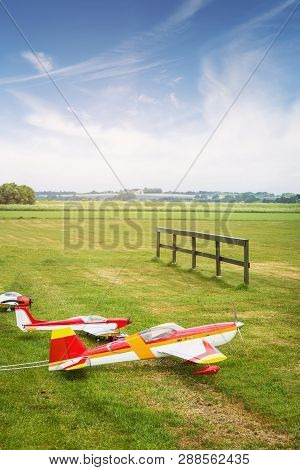 Model Airplanes Ona Line On A Green Field In The Summer Under A Blue Sky