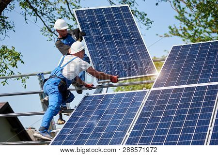Two Workers Mounting Heavy Solar Photo Voltaic Panel On Tall Steel Platform On Green Tree And Blue S