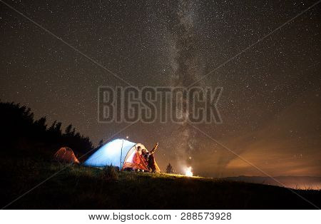 Night Summer Camping In The Mountains Near Forest. Happy Couple Hikers Having A Rest Together, Sitti
